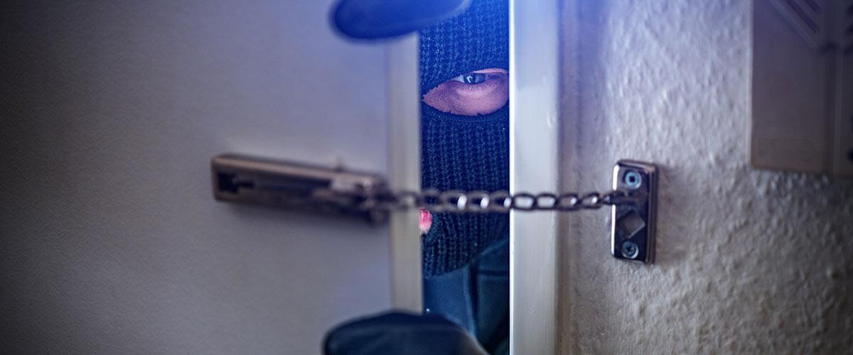 Maskierter Einbrecher in einer Haustüre